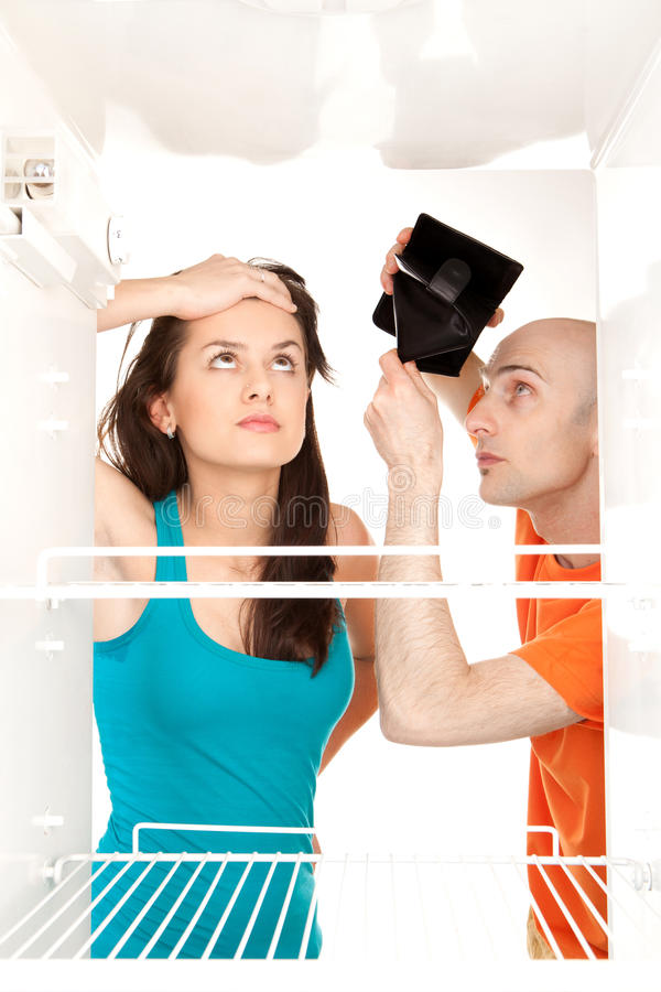 Empty wallet empty fridge. A couple with no money searching for food in an empty refrigerator whilst the man holds his empty wallet royalty free stock photos