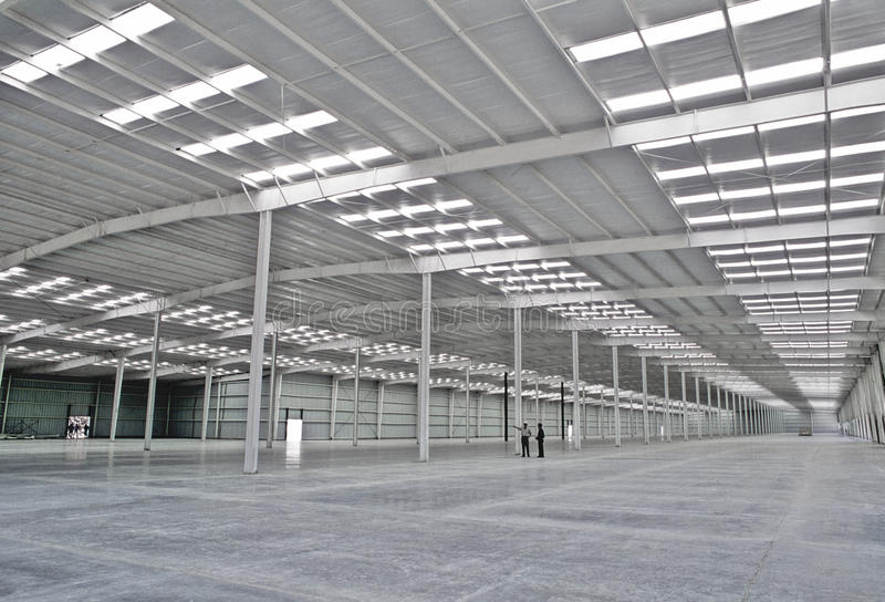 Empty warehouse with human figures royalty free stock photography
