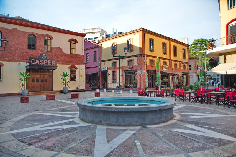 An empty waterfountain and old buildings. A picture of an empty waterfountain and buildings in the background,in an area in a Greek town Thessaloniki,Ladadika stock photography