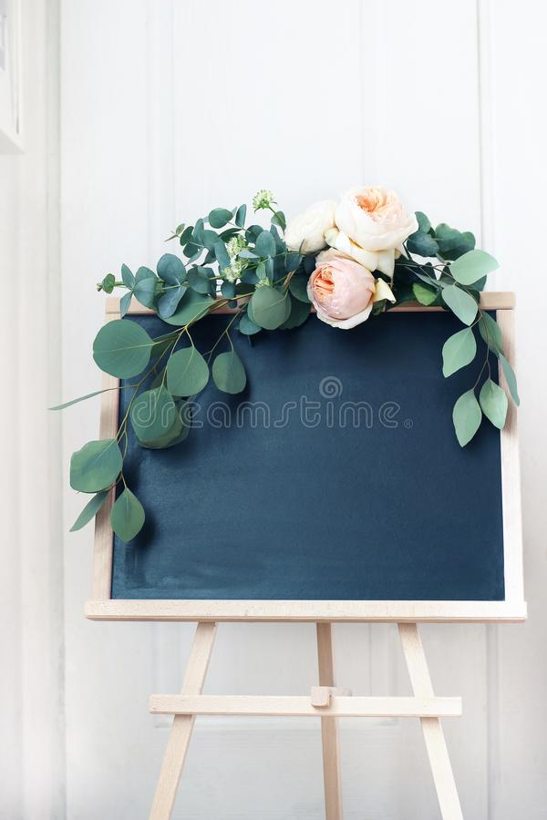 Empty wedding chalkboard sign mockup scene. Floral garland of eucalyptus branches and apricot English roses flowers royalty free stock photos