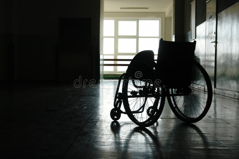 Empty wheelchair. Silhouette of empty wheelchair parked in hospital hallway royalty free stock photo