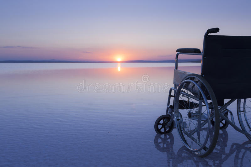 Empty wheelchair on the lake at sunset with beautiful colours stock photo