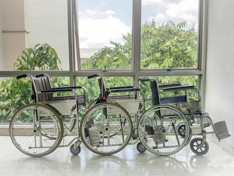 Empty wheelchair parked in front of hospital window. stock photo