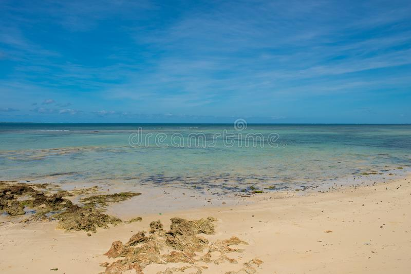 An empty white beach and shallow turquoise water under a sunny blue sky royalty free stock photos
