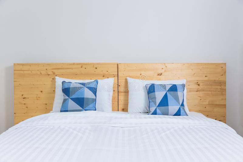Empty white bed with blue and white pillows and wooden headboard royalty free stock photography