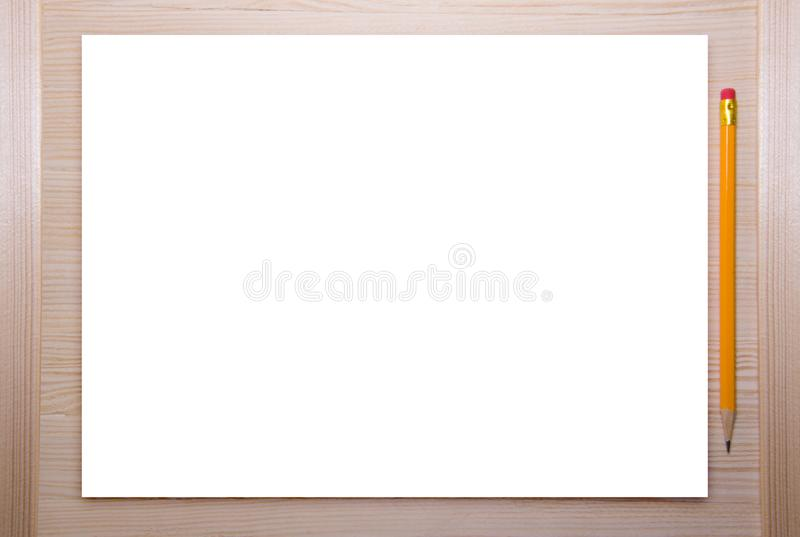 Empty white canvas frame with pencil on a wooden background. stock photography