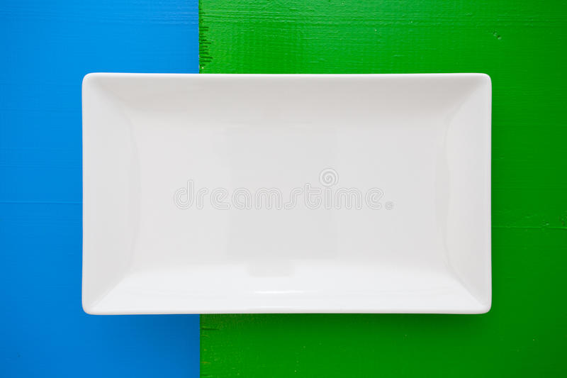 Empty white ceramic dish on over blue and green background, rectangle dish. Empty white ceramic dish on over blue and green wooden table,rectangle dish stock images