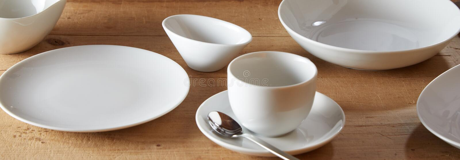 White ceramic tableware on wooden surface stock image