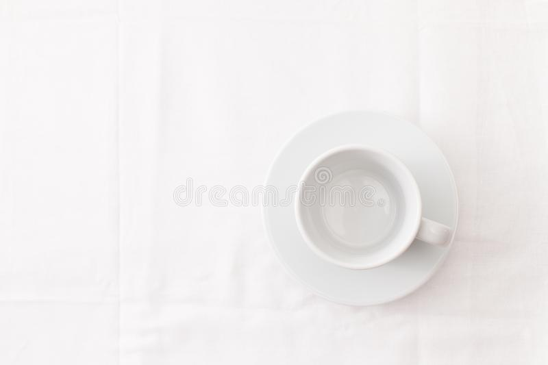 Empty white Cup of tea on white. Place for text. An empty Cup of tea on the table with a white tablecloth. Place for text. Background image royalty free stock images