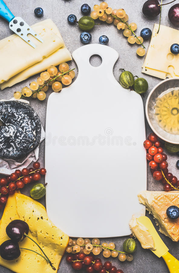 Empty White cutting board and Variety of Delicious cheese with berries and honey for dessert or Breakfast , top view stock photography