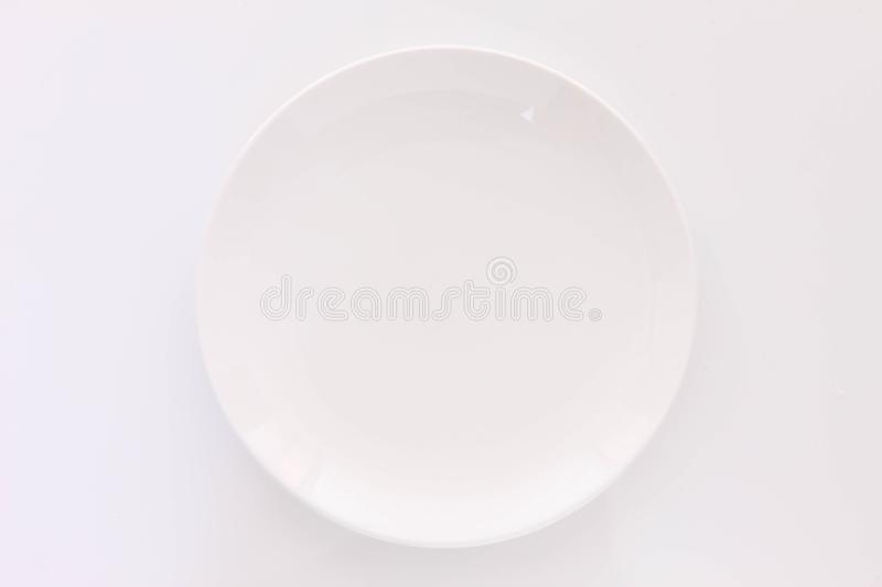 Empty white dish on the white table. Close Up Shot Of empty white dish on the white table royalty free stock photos