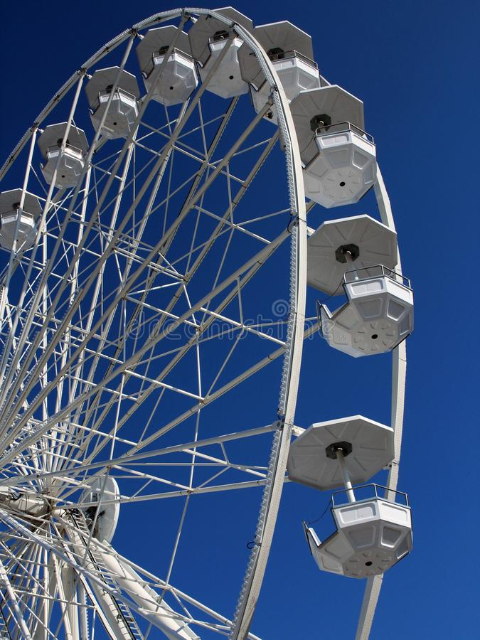 Empty white Ferris wheel spinning on blue sky background stock photos