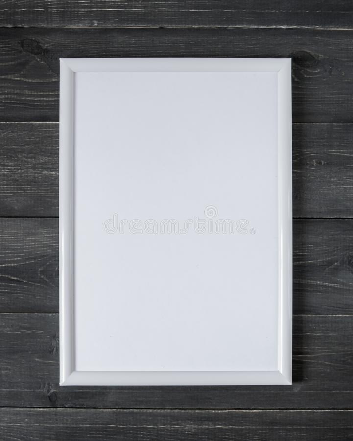 Empty white frame for a picture on a dark wooden background royalty free stock photography