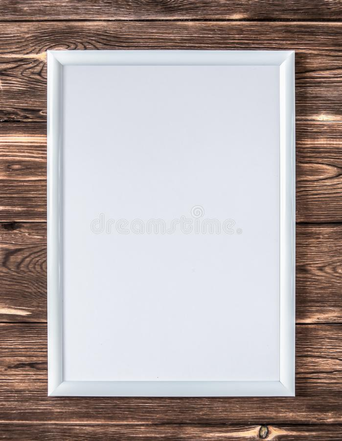 Empty white frame for a picture on a wooden brown background royalty free stock photos
