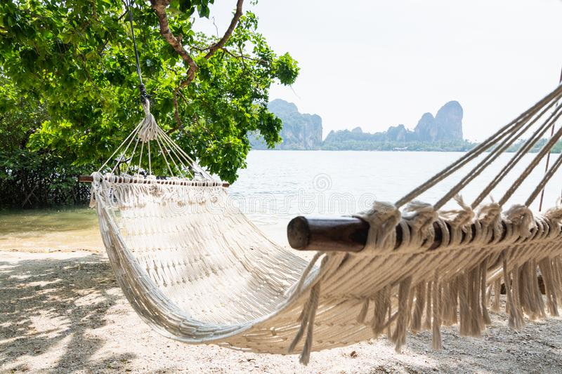 Empty white hammock at Krabi Railey beach overlooking the harbour and mountains, Thailand.  royalty free stock photo