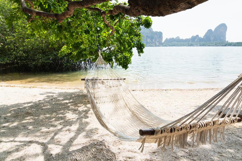 Empty white hammock at Krabi Railey beach overlooking the harbour and mountains, Thailand.  royalty free stock image