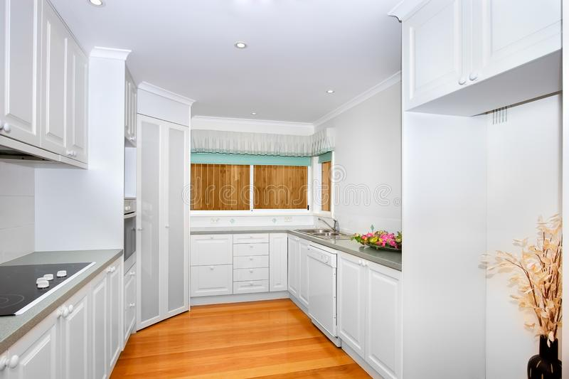 Empty white kitchen. With wooden floor, electric stove some cupboards and a sink royalty free stock photo