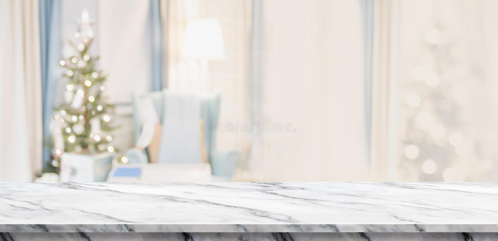 Empty white marble table top with abstract warm living room decor with christmas tree blur background with bokeh light,Holiday ba stock image