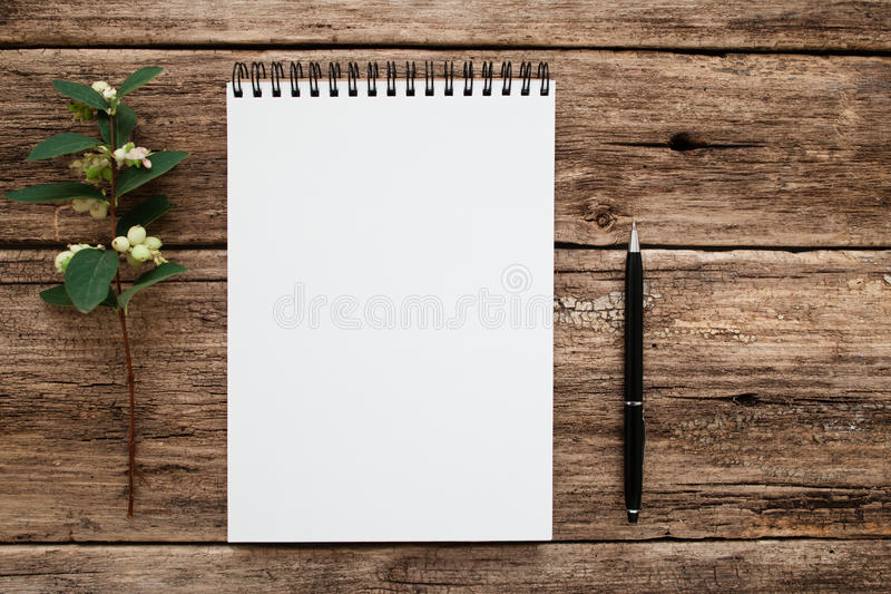 Empty white notebook with flowers and pen flat lay. Top view on blank sketchbook on grunge old wooden background, free space. Art, writing, idea, memory stock images