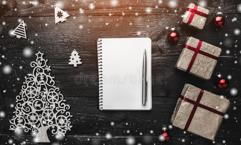 Empty white notebook and pen on black background of christmas gifts, ornamented wooden toys and snowflakes. Top view stock image
