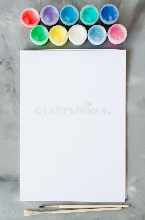 Empty white paper sheet, brushes and paints. Mock up for drawing stock photo