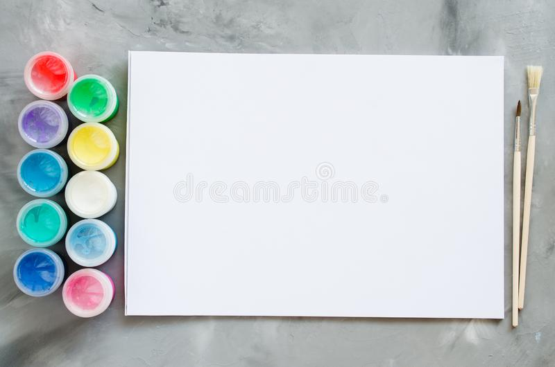 Empty white paper sheet, brushes and paints. Mock up for drawing royalty free stock photos