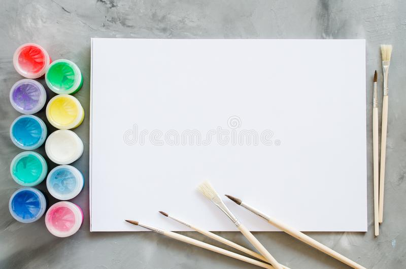 Empty white paper sheet, brushes and paints. Mock up for drawing royalty free stock photo