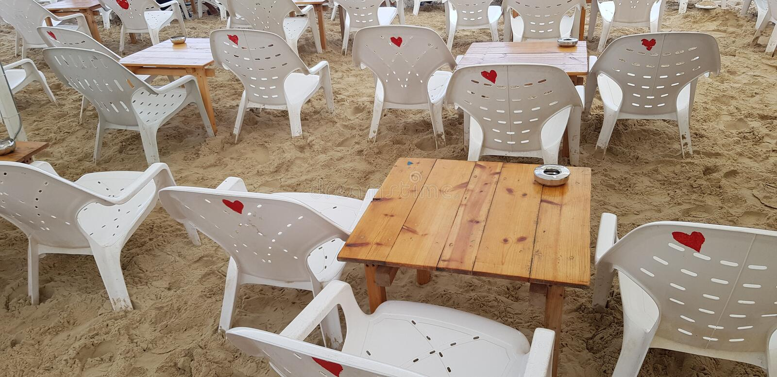 Empty white plastic chairs and wooden tables royalty free stock images
