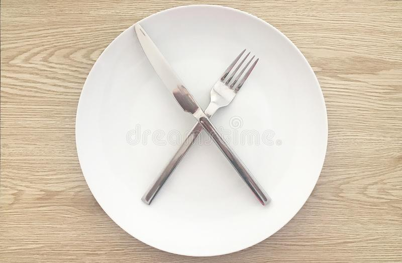 Modern White Plate and Silverware with Natural Wood Background royalty free stock photography