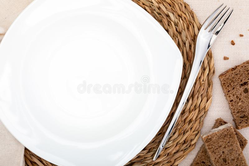 Empty white plate. On delicate beige tablecloth. Concept to include your food and your text royalty free stock image
