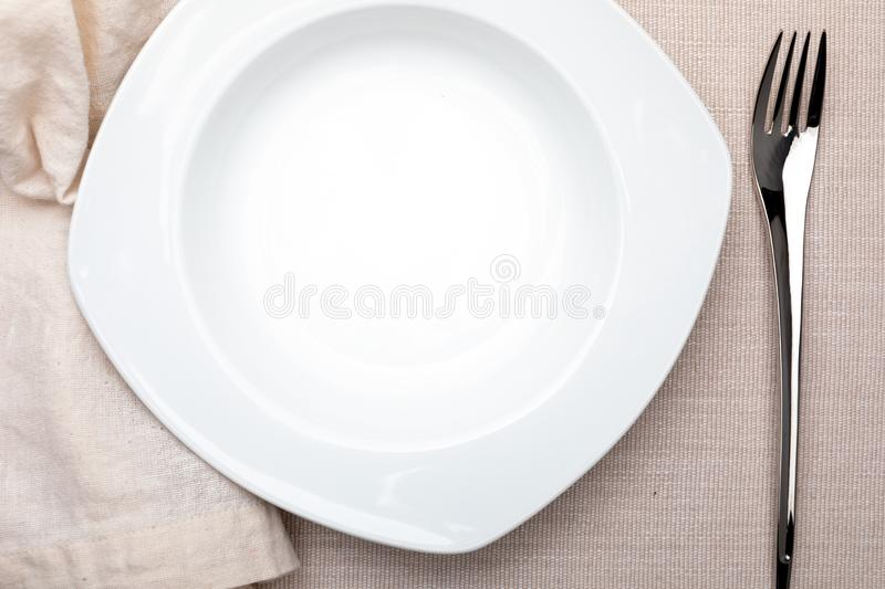 Empty white plate. On delicate beige tablecloth. Concept to include your food and your text stock image