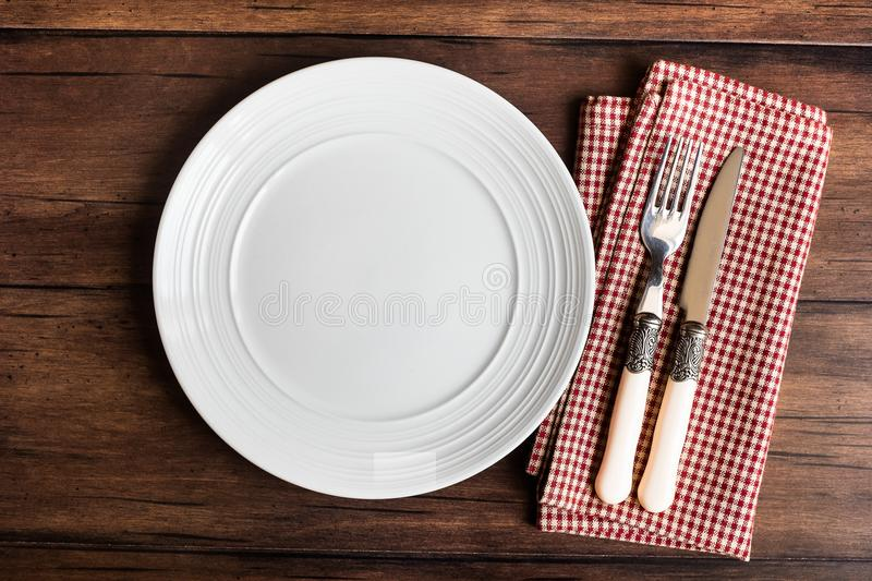 Empty white plate, fork and knife on a checkered red napkin on an old wooden brown background, top view. Image with copy space. Ki stock image