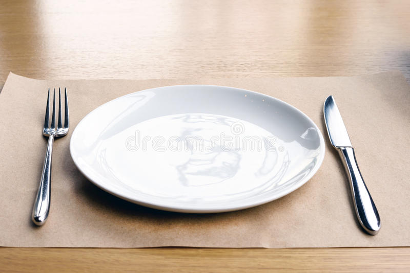Empty white plate. Fork and knife, on a wooden table in a restaurant stock photography