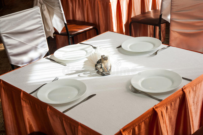 Empty white plate in a formal table setting on a table set stock photography