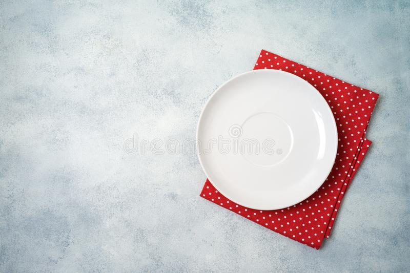 Empty white plate with tablecloth on gray stone table background. Top view from above royalty free stock photos