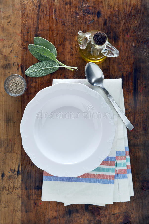 empty white plate on a towel on a wooden texture background. olive oil.space for writing text royalty free stock photos