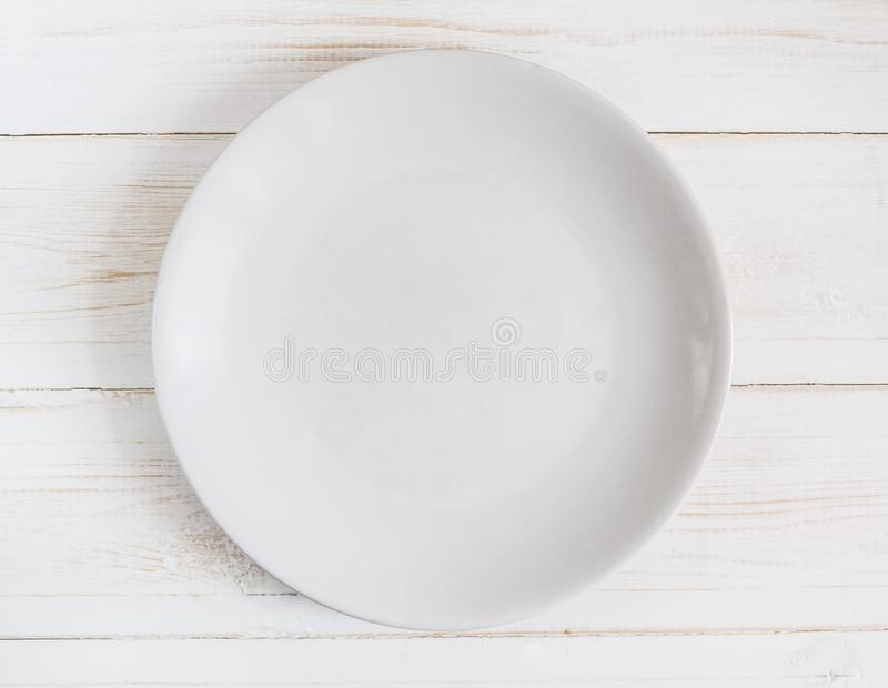 Empty white plate on white wooden background royalty free stock images