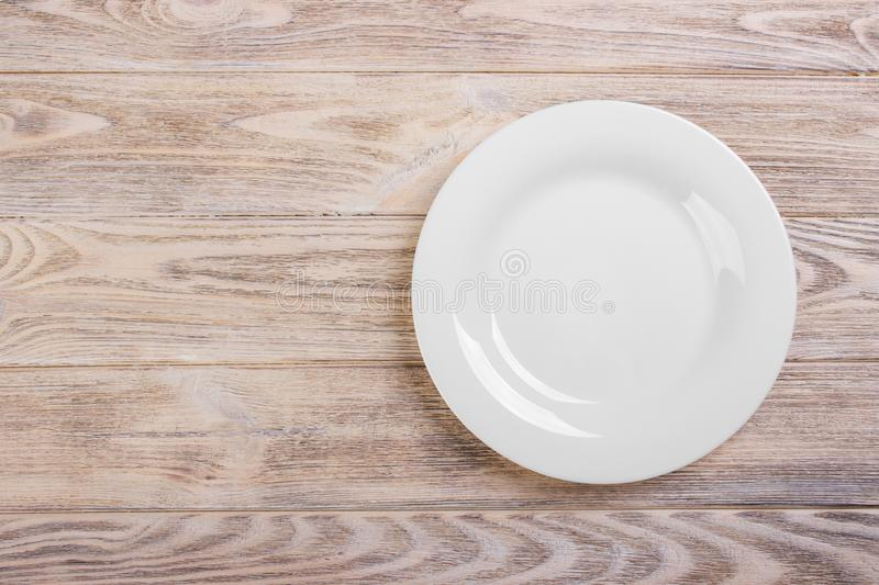 Empty white plate on wooden table. Template for your design royalty free stock photos
