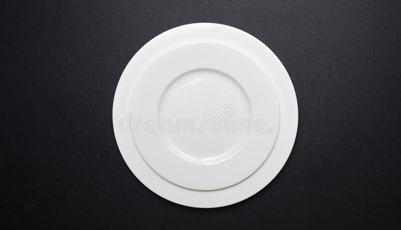 Empty white plates on black color background stock photos