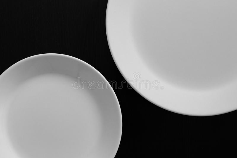 Empty white plates on black wooden table stock image