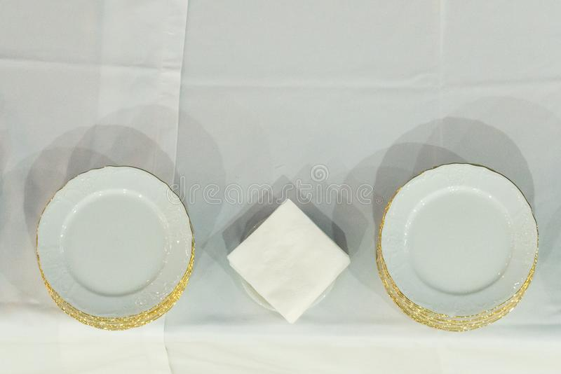 Empty white plates dish with gold trim on white table. Blank, dining, dinner, meal, food, nobody, object, space, utensil, background, kitchen, circle, clean stock image