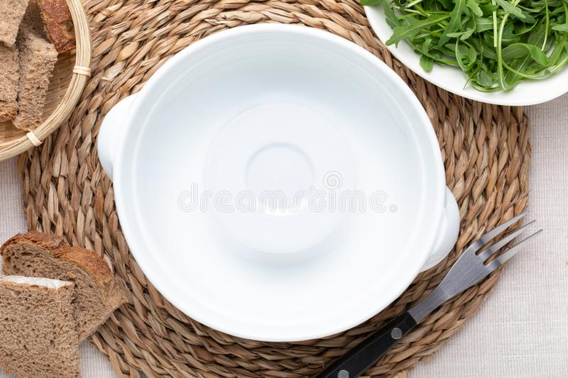 Empty white pot. On delicate beige tablecloth. Includes bread and green arugula. Concept to include your food and your text stock image