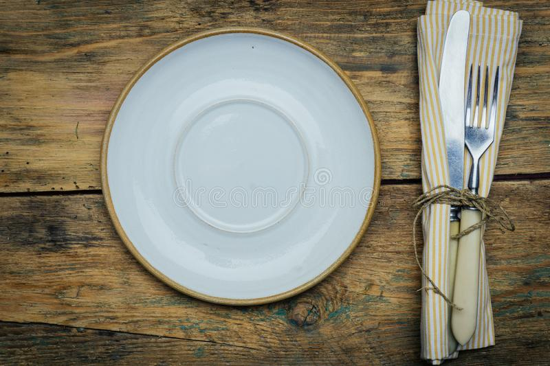 Empty white rustic plate on old wooden background with knife, fork and napkin. Rustic food concept. stock photography