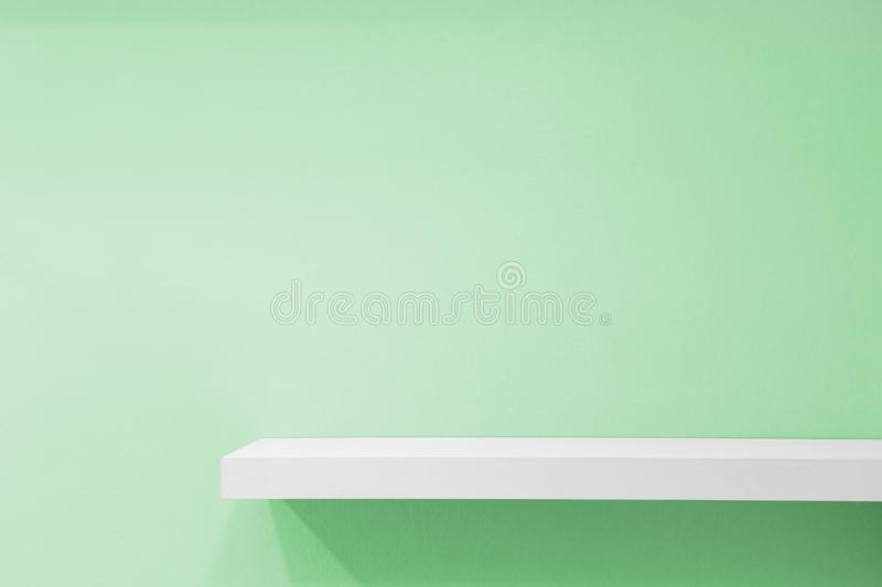 Empty white shop shelf, retail shelf on green vintage background stock images