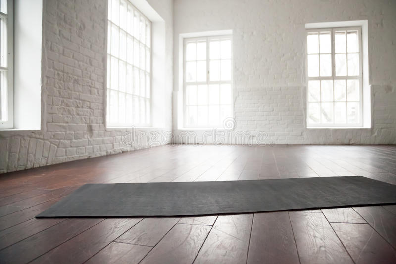 Empty white space, loft studio, yoga mat on the floor. Empty white space in fitness center, white brick walls, natural wooden floor and big windows, modern loft stock images
