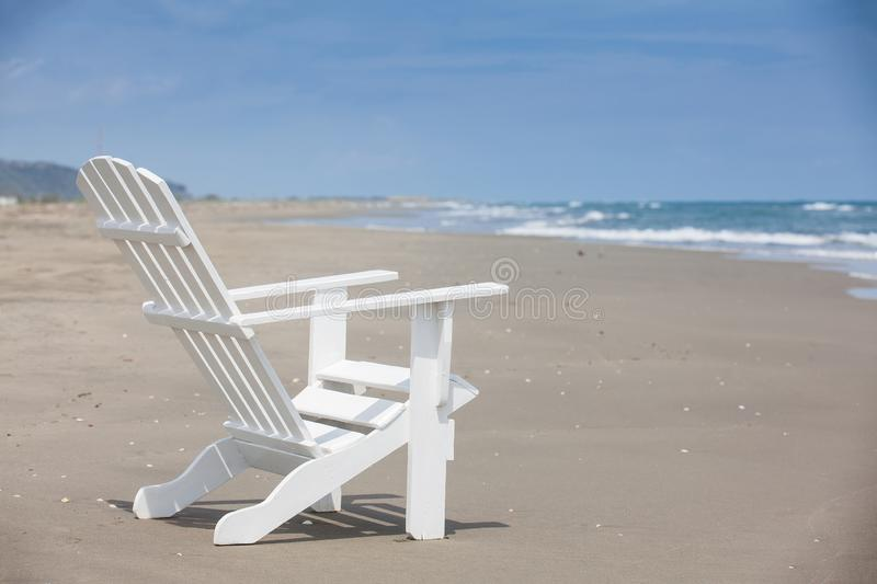 Empty white wooden chair at a paradisiac beach on the tropics in a beautiful sunny day. In Cartagena de Indias stock photo