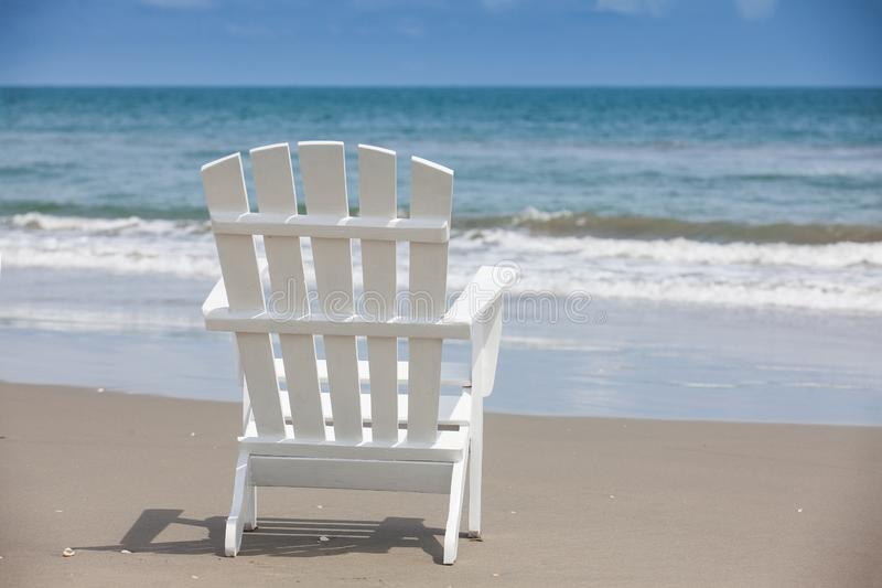 Empty white wooden chair at a paradisiac beach on the tropics in a beautiful sunny day. In Cartagena de Indias royalty free stock image