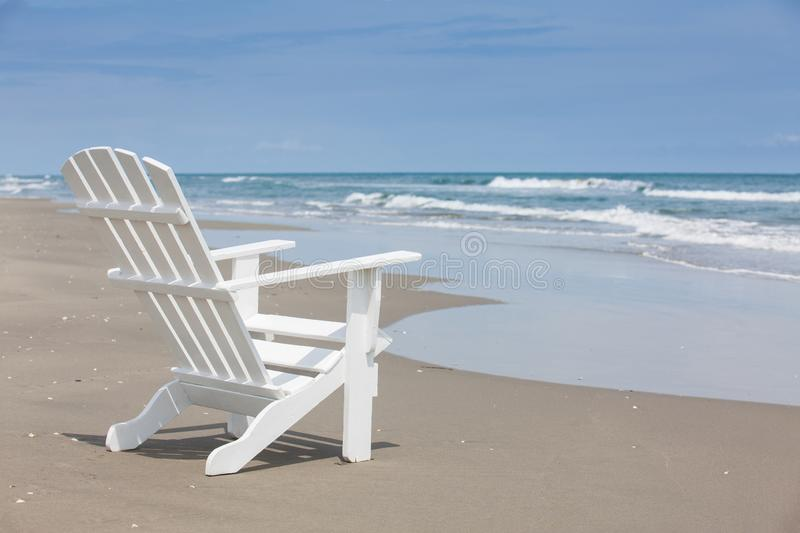 Empty white wooden chair at a paradisiac beach on the tropics in a beautiful sunny day. In Cartagena de Indias royalty free stock photos