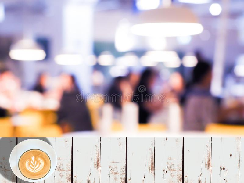 Empty white wooden table space platform with Vintage tone abstract blur image of Cafe or Restaurant on night. Time with bokeh for background usage royalty free stock photo
