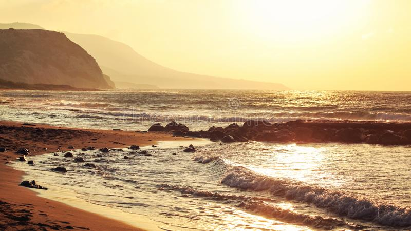 Empty wild beach lit by golden sunset. Small waves over rock, hills in hazy background royalty free stock photo